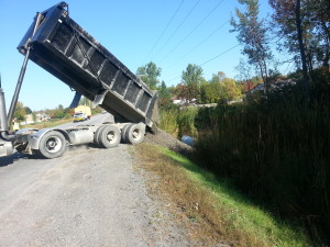 Dumptruck covering culvert with stone.